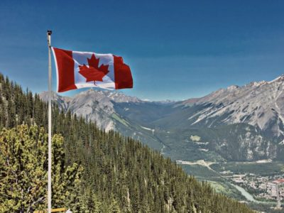 Canadian Flag blowing in the wind Over Mountains